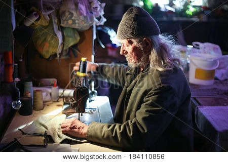Old Man Sewing Cloth