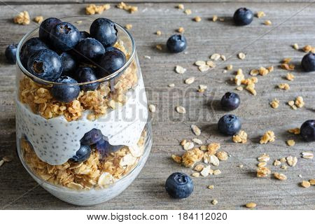 glass of blueberry yogurt parfait or chia pudding with berries, granola, oats and chia seeds. healthy breakfast. close up