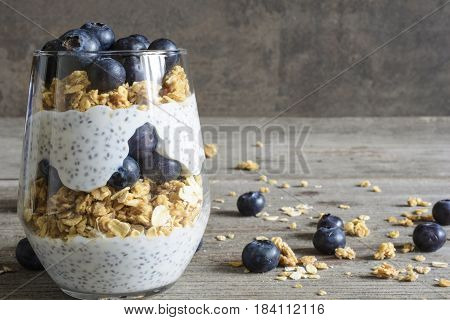 chia pudding or yogurt parfait with blueberries, granola and chia seeds on rustic wooden background. healthy breakfast
