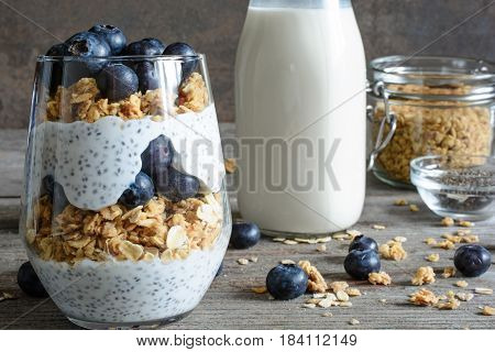chia pudding or yogurt parfait with blueberries granola and chia seeds on rustic wooden background with bottle of milk. healthy breakfast
