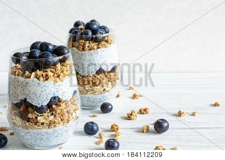 blueberry yogurt parfait with granola oats and chia seeds in glasses on white wooden table. healthy breakfast. close up