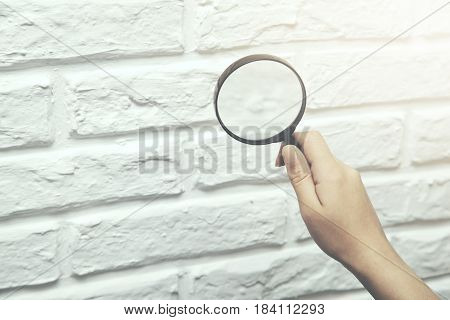 Female hand with magnifying glass on brick wall