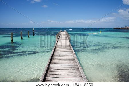 Wood jetty perspective into the turquoise-green Indian Ocean seascape with pilings under a blue sky at Rottnest Island in Western Australia.