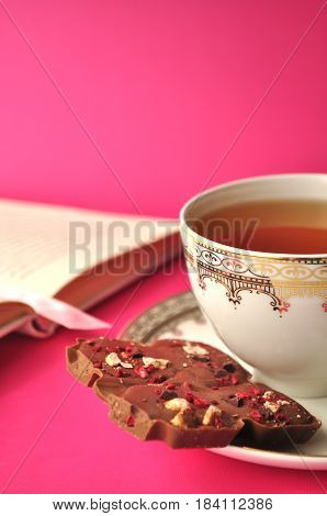 Gold and white porcelain tea cup and saucer with artisan chocolate and open book on bright fuchsia pink background with copy space