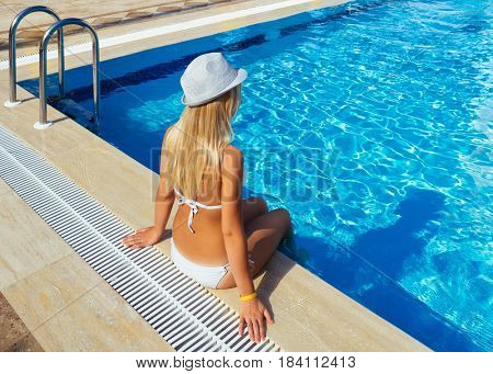 Blond girl is resting in a summer resort. Swimming pool near the tourist hotel. Sunny day