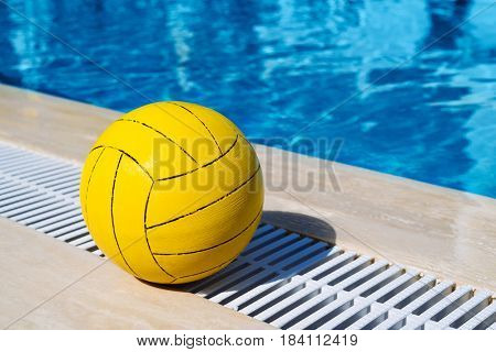 Summer games in the pool. Yellow ball on a background of blue water in a sunny resort