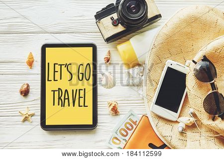 Travel. Let's Go Travel Text Sign Concept On Yellow Tablet Screen, Camera Sunglasses  Passport Money