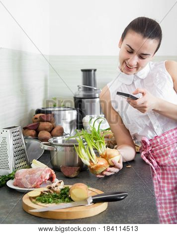 The Girl Prepares Food In The Kitchen With The Phone