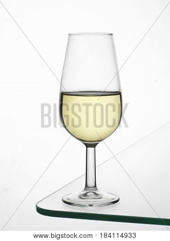 Glass of fine wine with fine wine on glass table