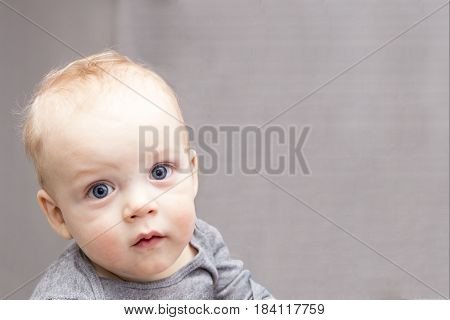 Blue-eyed baby boy looking at camera with reproach. Open-eyed cute infant kid. Copy space.