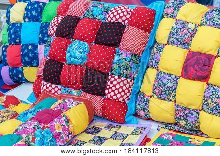 Are pillows potholders wraps are handmade. A variety of patterns in the form of cells squares of different color combinations. Patterns with flowers polka dots grass sunflowers.