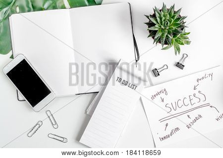 business plan development with mobile and copybook on white office desk background top view mock-up