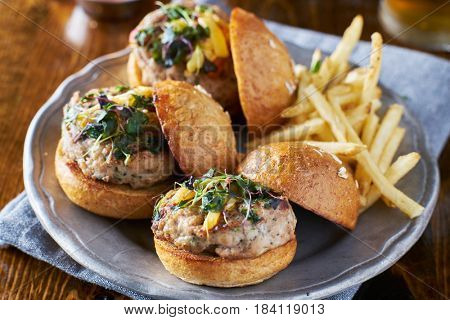 three turkey burger sliders with fries on plate