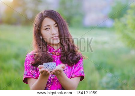 Young Chinese smiling girl pouring tea In traditional Chinese clothes outdoors. Traditional chinese tea ceremony accessories