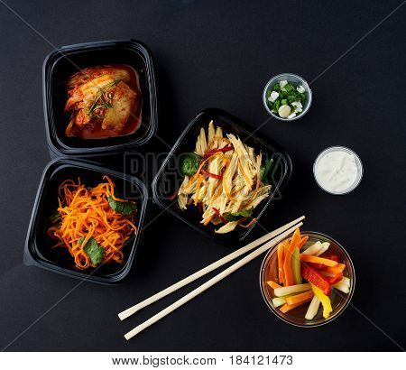 Korean cuisine. Set of salads on black background. Asparagus, korean carrot, kaktugi, fresh vegetable sticks and green onion.
