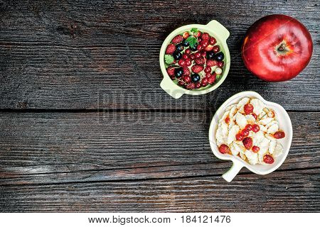 Bowl of corn flakes, apple and berries on the dark wooden surface. Flat lay.