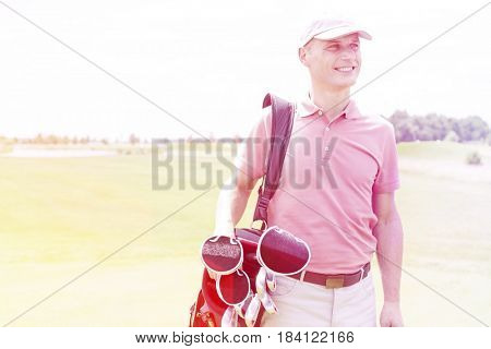 Happy middle-aged man looking away while carrying golf bag