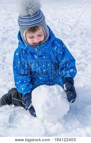 Small boy rolling a snowball. A snowball for a snowman. Boy smiling. He is wearing a blue jacket black snow pants and a hat.