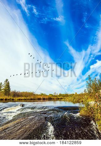 Foam water rapids on the smooth stones of the Winnipeg River. Cirrus clouds . The concept of travel