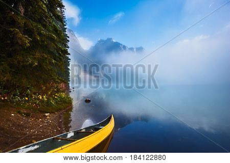 Fishing boats moored on the shore. Foggy morning on Emerald Lake. Canada, Yoho National Park
