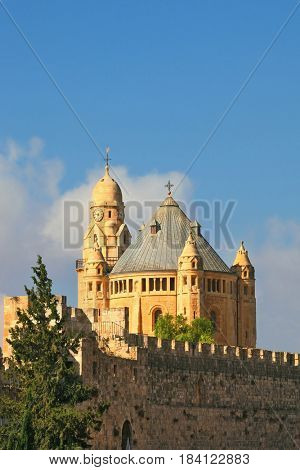 The morning sun illuminates the dome and the tower of the abbey.  The Catholic Church of Dormition in Jerusalem.