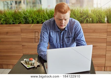 An Unsatisfied Young Businessman With Red Hair And Stylish Haircut Having Lunch Break In Modern Cafe