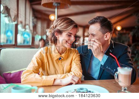 Smiling love couple at romantic date in restaurant