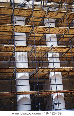 Metal scaffolding with wooden decking built around a historic building with columns for restoration work and renovation of the facade. Construction works. Building construction.