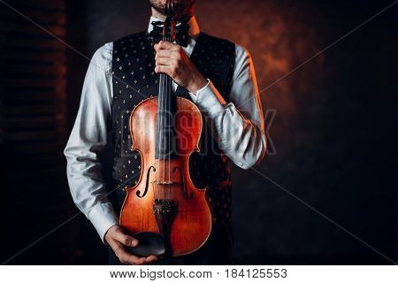 Portrait of male person holding wooden violin