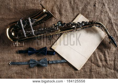 Saxophone, notes and bowtie on canvas background