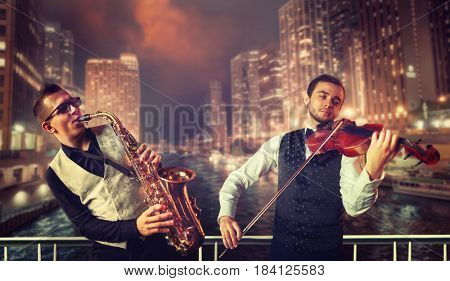 Saxophonist and violinst against night cityscape