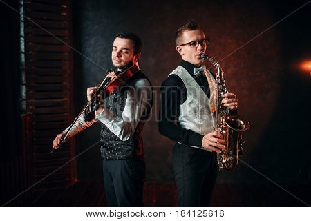Saxophonist and violinst playing classical melody