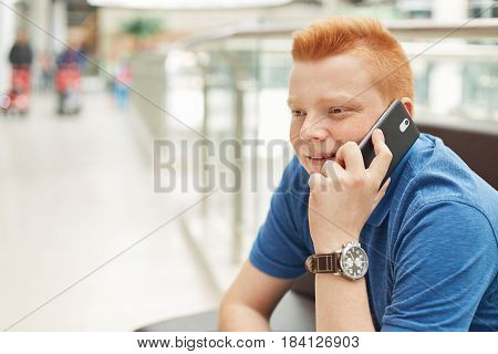 A Happy Redhead Man With Freckles Wearing Casual Blue T-shirt And Elegant Watch Having Rest In Shopp