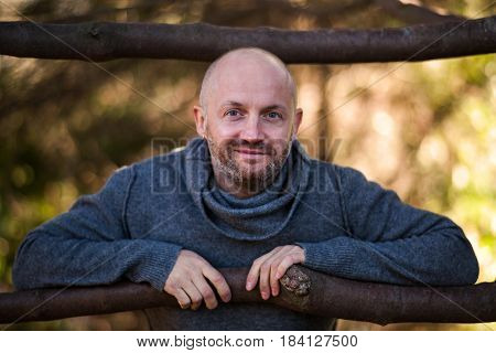 A Brutal Bald Man In A Sweater Sits And Rests On The Nature