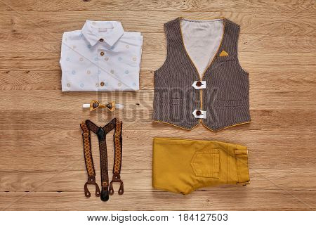 Top view photo of the boy's clothes on the wooden background. White shirt with print, brown vest, bowtie, brown pants and suspenders. Cute clothes for little boys. Concept of the children's fashion. Summer or spring children's clothes.