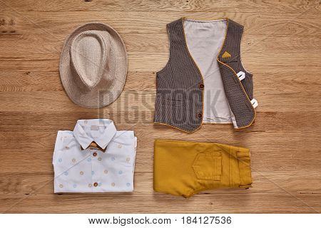 Top view photo of the boy's clothes with accessories on the wooden background. White shirt with print, brown vest, bowtie, brown pants and hat. Cute clothes for little boys. Concept of the children's fashion.