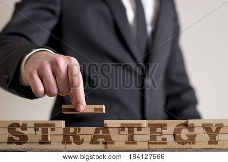 Businessman building a structure of wooden bricks while assembling word Strategy.