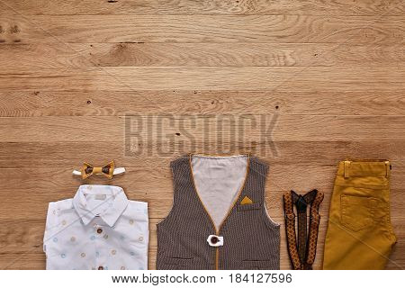 Top view photo of the boy's clothes on the wooden background. White shirt with print, brown vest, bowtie, brown pants and suspenders. Cute clothes for little boys. Concept of the children's fashion. Summer or spring childrens clothes.