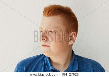 A Sideways Portrait Of Thoughtful Redhead Boy With Trendy Hairdo And Freckles Wearing Casual Blue Sh