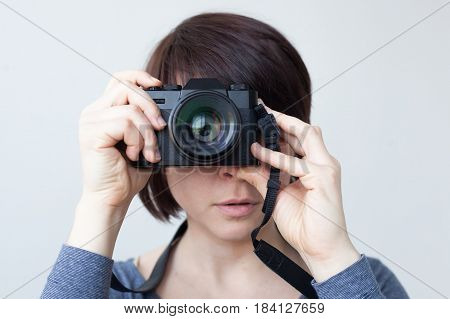 A girl is holding a camera by her face. The lens looks like a big eye. Hobby with photography