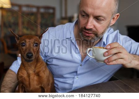 dog is resting with its owner. A brutal man listens to someone with distrust and doubt