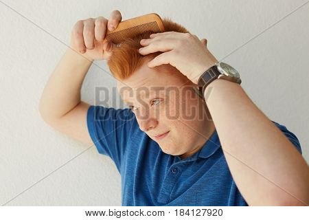 A Redhead Boy With Freckles Dressed In Blue Casual Shirt Brushing Hair With Comb On White Background
