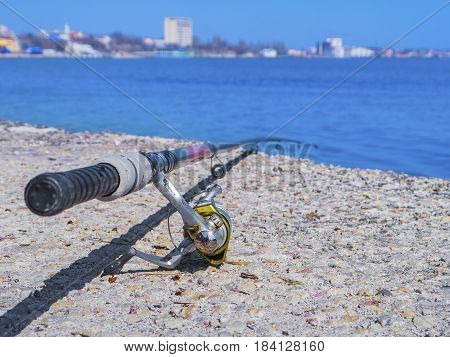 Fishing rod lies on the shore near the ocean