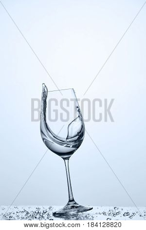 Water splashing from tilted wineglass with cleaner water while standing on the glass with draps against light background. Clean water. Care for the environment. Freshness and cleanliness. Concept of the healthy lifestyle.