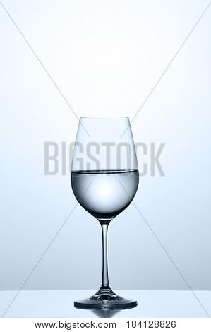 Cleaner water in the fixed wineglass while standing on the clean glass against light background. Property and quiet. Clarity and transparency. Care for the environment. Perfectly. Concepth of the healthy lifestyle.