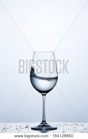Pure water wave in the wine glass while standing on the glass with drapes against light background. Environmentally friendly product. Cleaner and useful water. Care for environment. Concept of the healthy lifestyle.