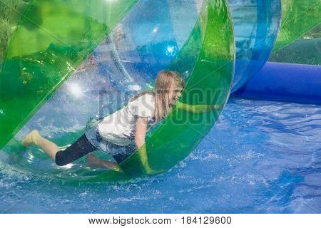 Cheerful girl playing in an inflatable plastic balloon on the water