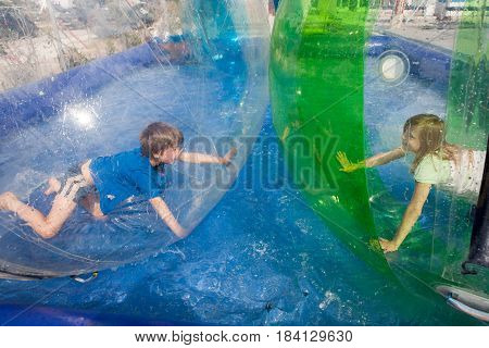 Two children having fun in an inflatable plastic balloon on the water