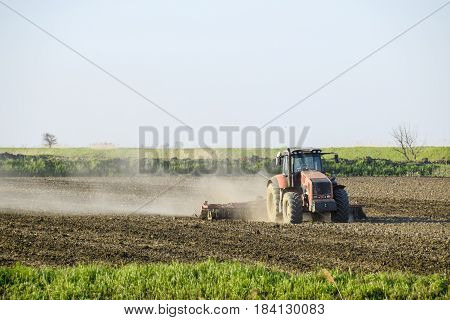 A Tractor With A Plow Lays The Soil. Soil Cultivation On The Fie