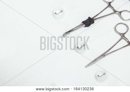 Piercing professional table with grips forceps and jewels. Overhead shot